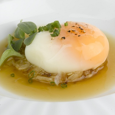 Foto: Huevo cocinado a baja temperatura, sobre berza, y un caldo untuoso de panceta